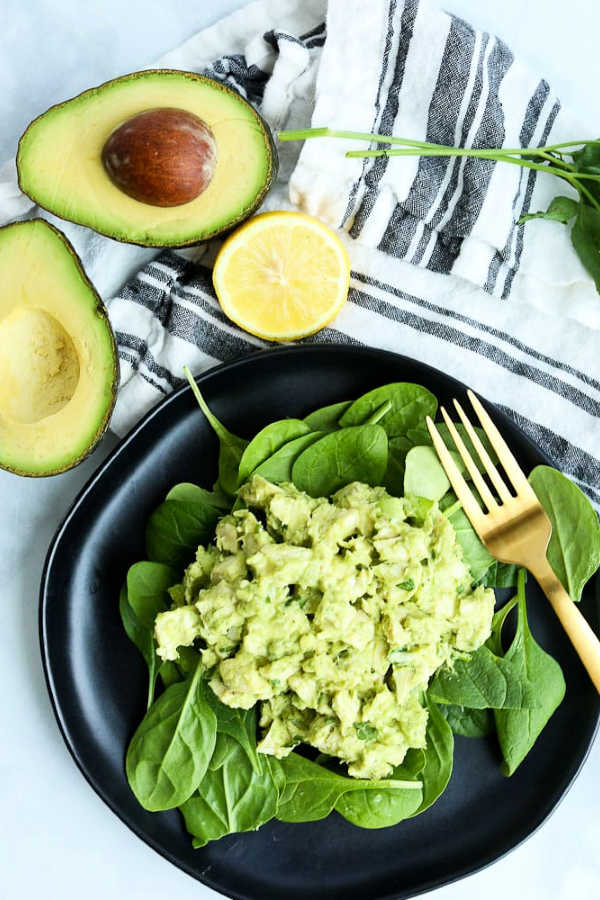 Avocado Chicken Salad over green leaves on a black plate wit avocado and lemon