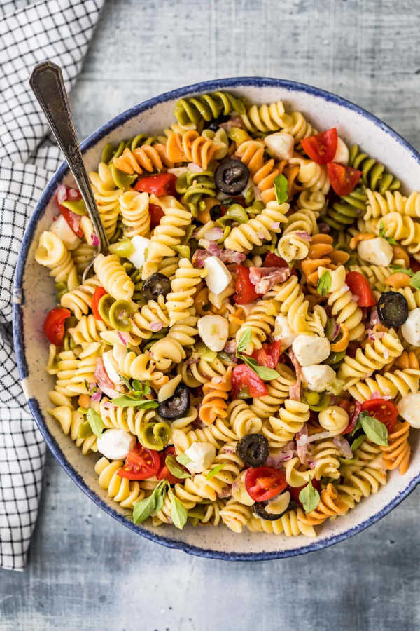 Classic Italian Pasta Salad in a bowl with tri-colored rotini pasta, cherry tomatoes, red onions, salami, mozzarella and olives.