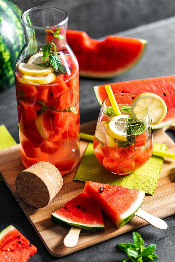 Fresh Watermelon lemonade recipe for a glass and pitcher with lemon pieces and mint leaves