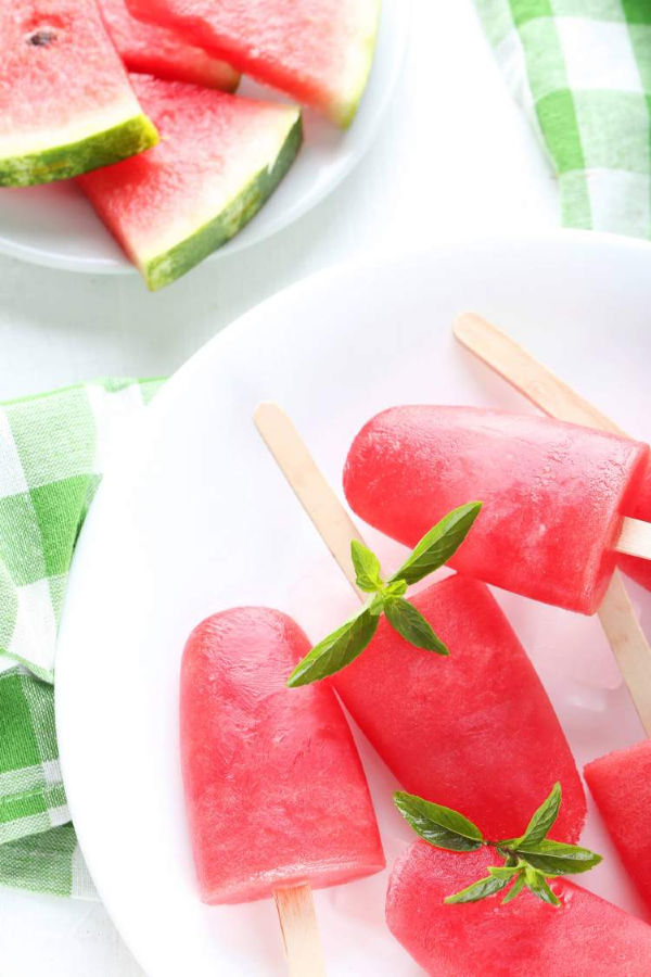 Healthy Watermelon Popsicles for summer on a plate with pieces of watermelon and mint leaves