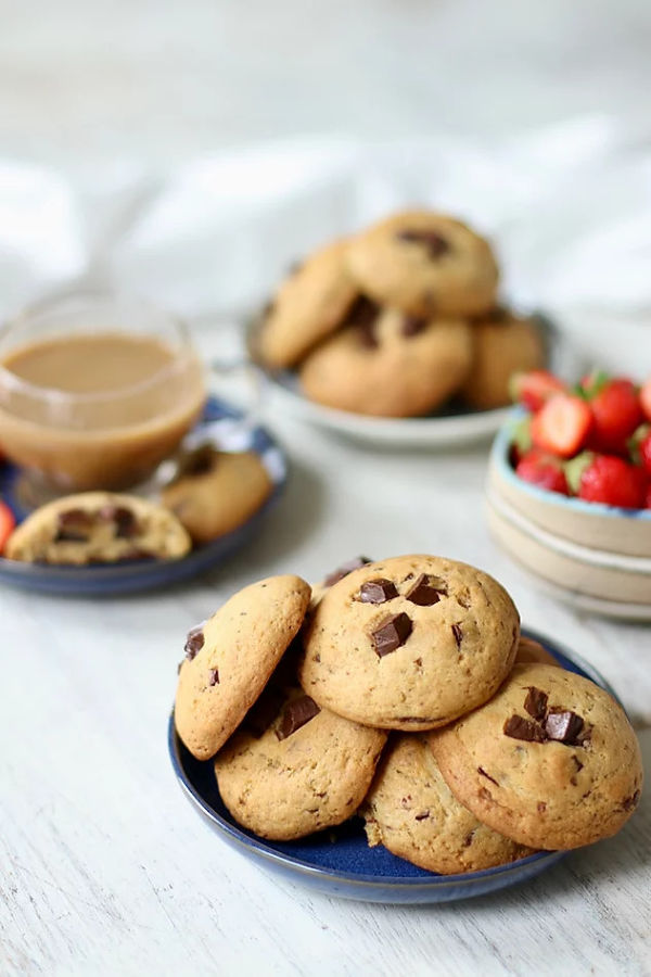 Vegan Chocolate Chip Cookies on a blue plate with coffee and strawberries